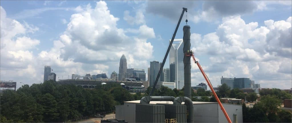 Installing industrial stack with Charlotte. NC, in background